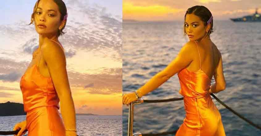 Singer Rita Ora went braless in an orange satin gown during the festive season.