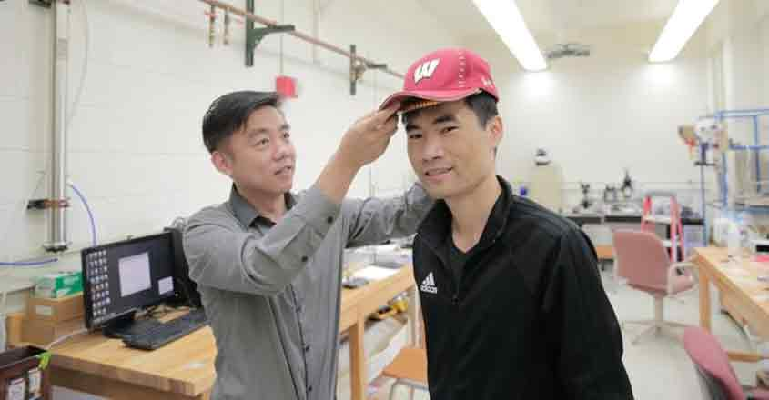 University of Wisconsin-Madison Materials Science and Engineering Professor Xudong Wang (left) and colleagues developed a device -- unobtrusive enough to fit under a cap -- that harnesses energy from the wearer and delivers gentle electric pulses to stimulate dormant hair follicles and regrow hair. (Photo: UW-Madison by Sam Million-Weaver)