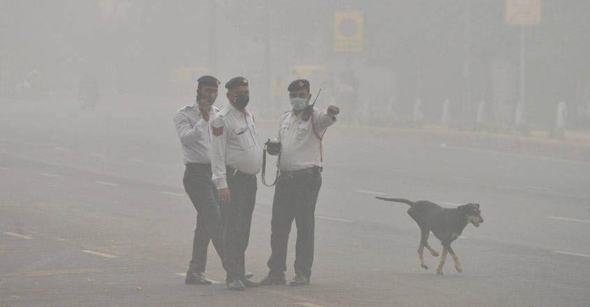 New Delhi: Traffic police personnel wear masks to protect themselves from pollution as smog engulfs New Delhi on Nov 3, 2019. (Photo: IANS)