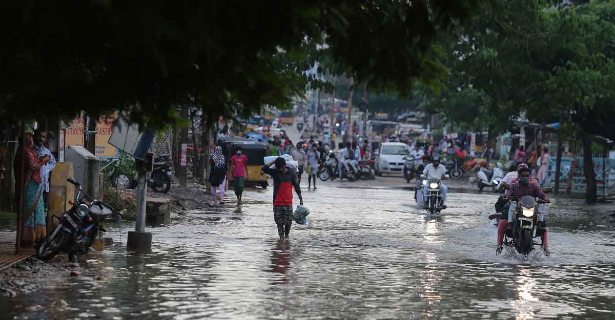 Commuters wade through receding floodwaters after heavy rainfall in Hyderabad