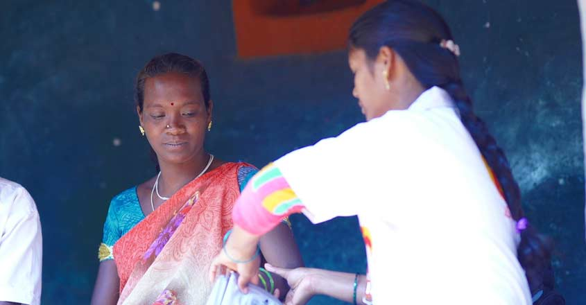A midwife conducting basic tests on a pregnant woman.
